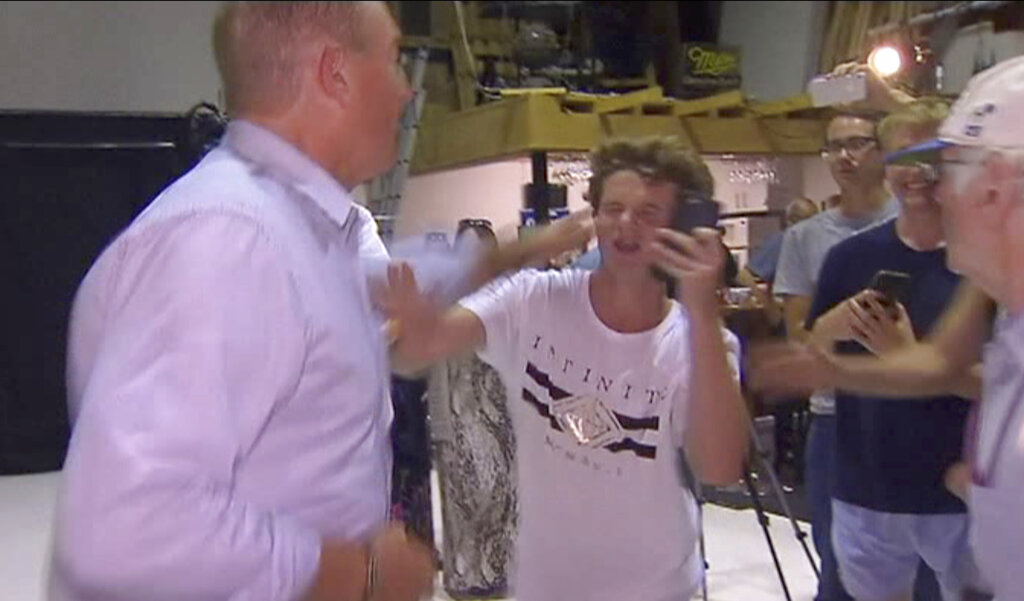 In this image made from video, Senator Fraser Anning swipes at a teenager who broke an egg on his head while he was holding a press conference on March 16, 2019, in Melbourne.