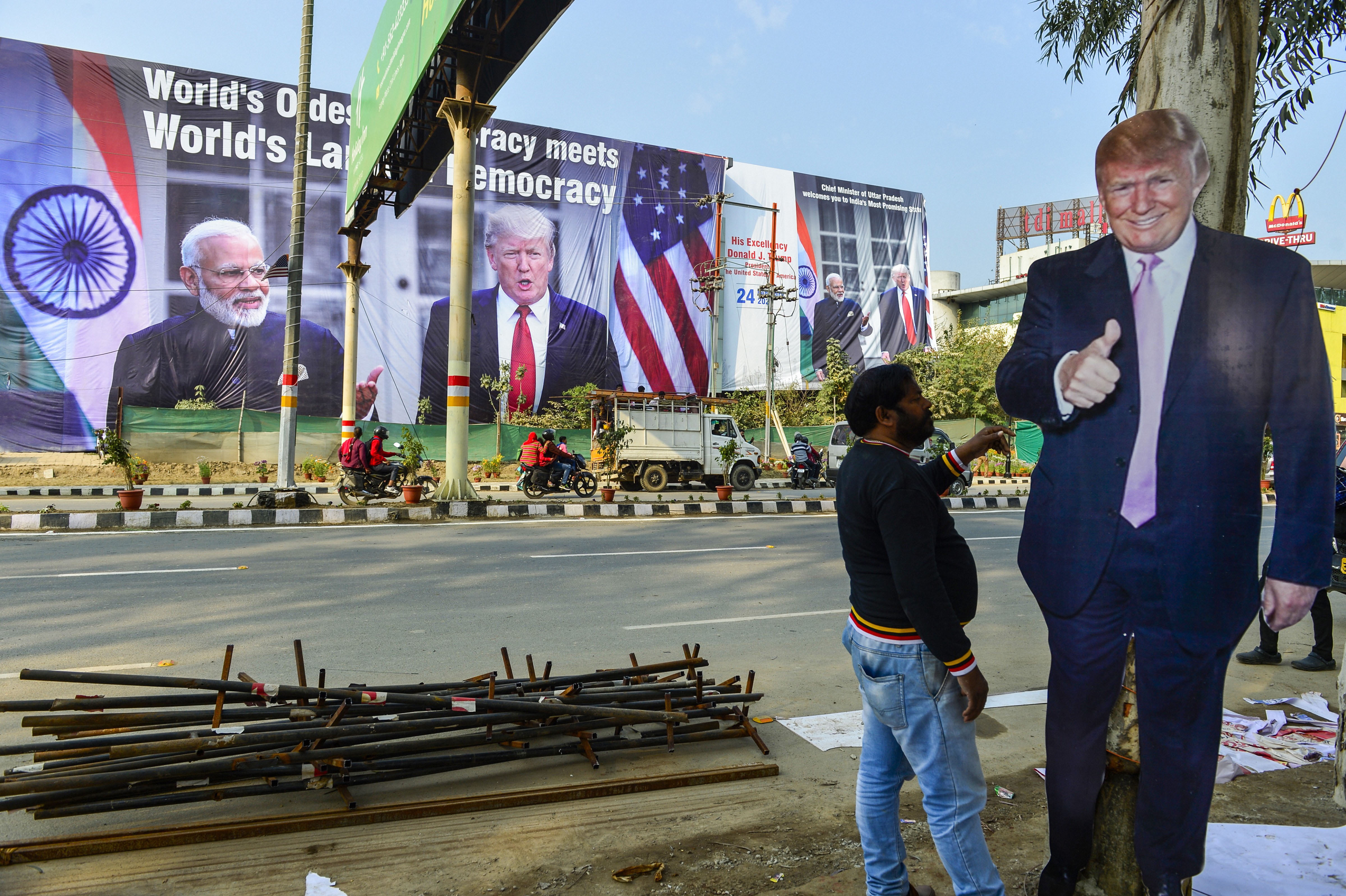A worker arranges billboards of Donald Trump, near Taj Mahal ahead of the US President's maiden visit to India, in Agra, Sunday, February 23, 2020