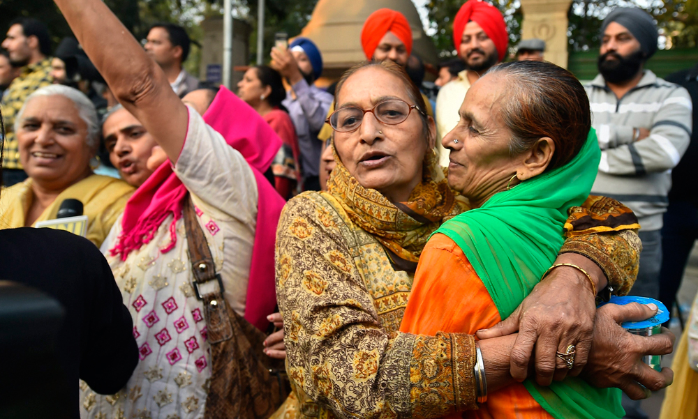 Family members of the victims of 1984 anti-Sikh riots celebrate outside the Patiala House Court in New Delhi on Tuesday, after the pronouncement of the first death punishment in the case.