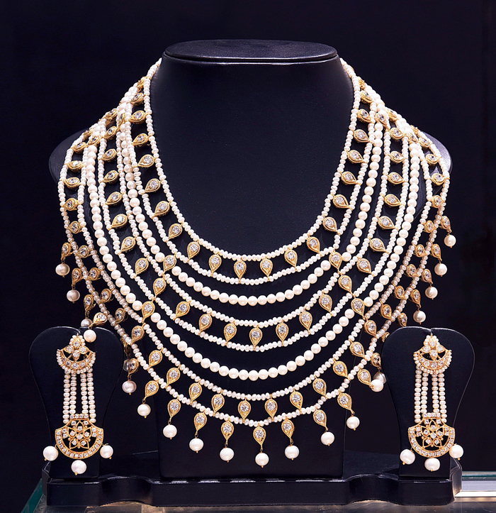 Go for a dazzling look by teaming these multilayered neckpiece, earrings and bangles with a bright red traditional sari. The neckpiece is made of white round freshwater pearls and cubic zircons studded on gold-polished silver alloy.  Rs 40,500 @ Chandrani Pearls
