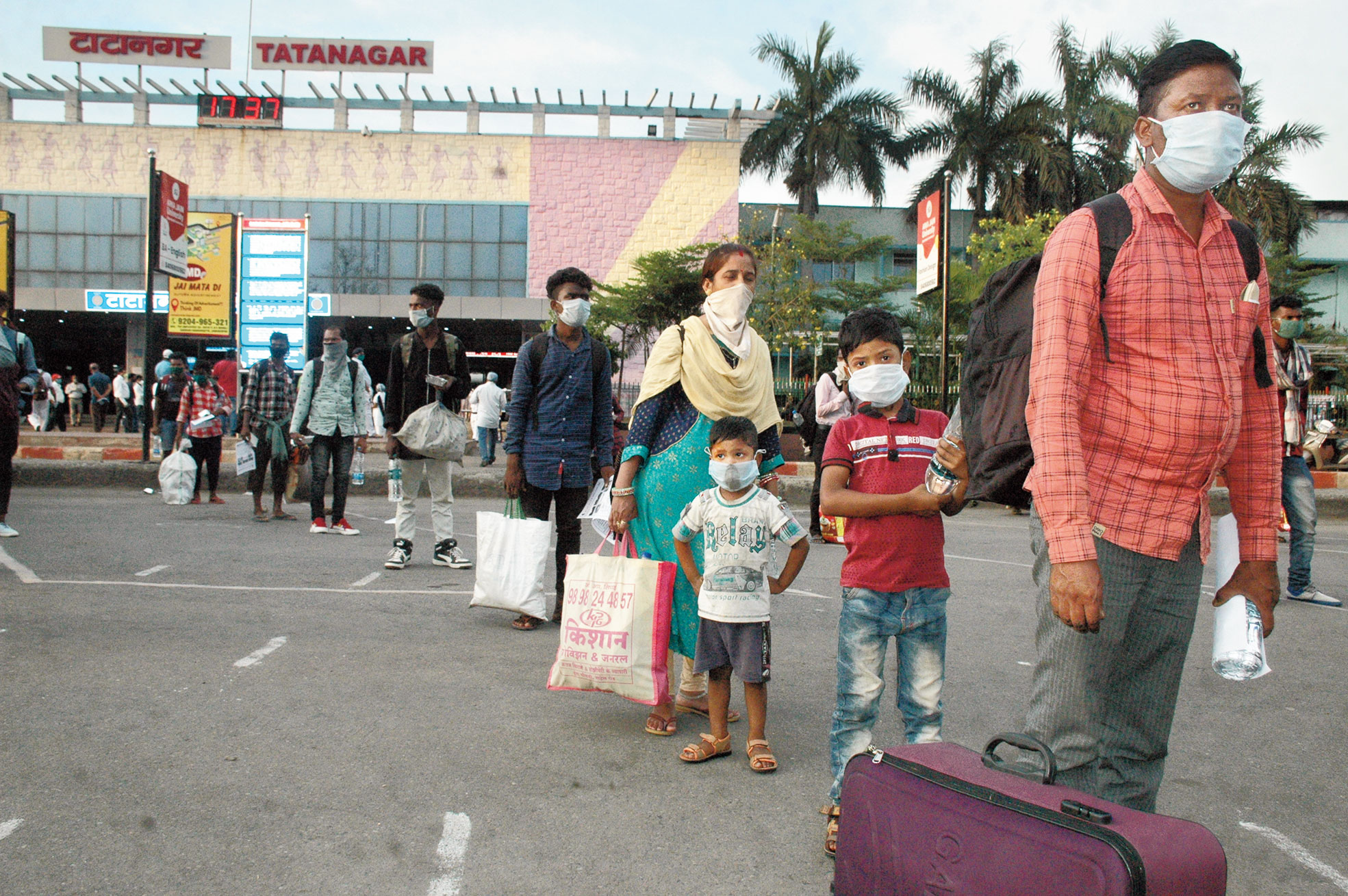 Migrant workers from Gujarat wait to board a bus outside Tatanagar station in Jamshedpur on Friday.