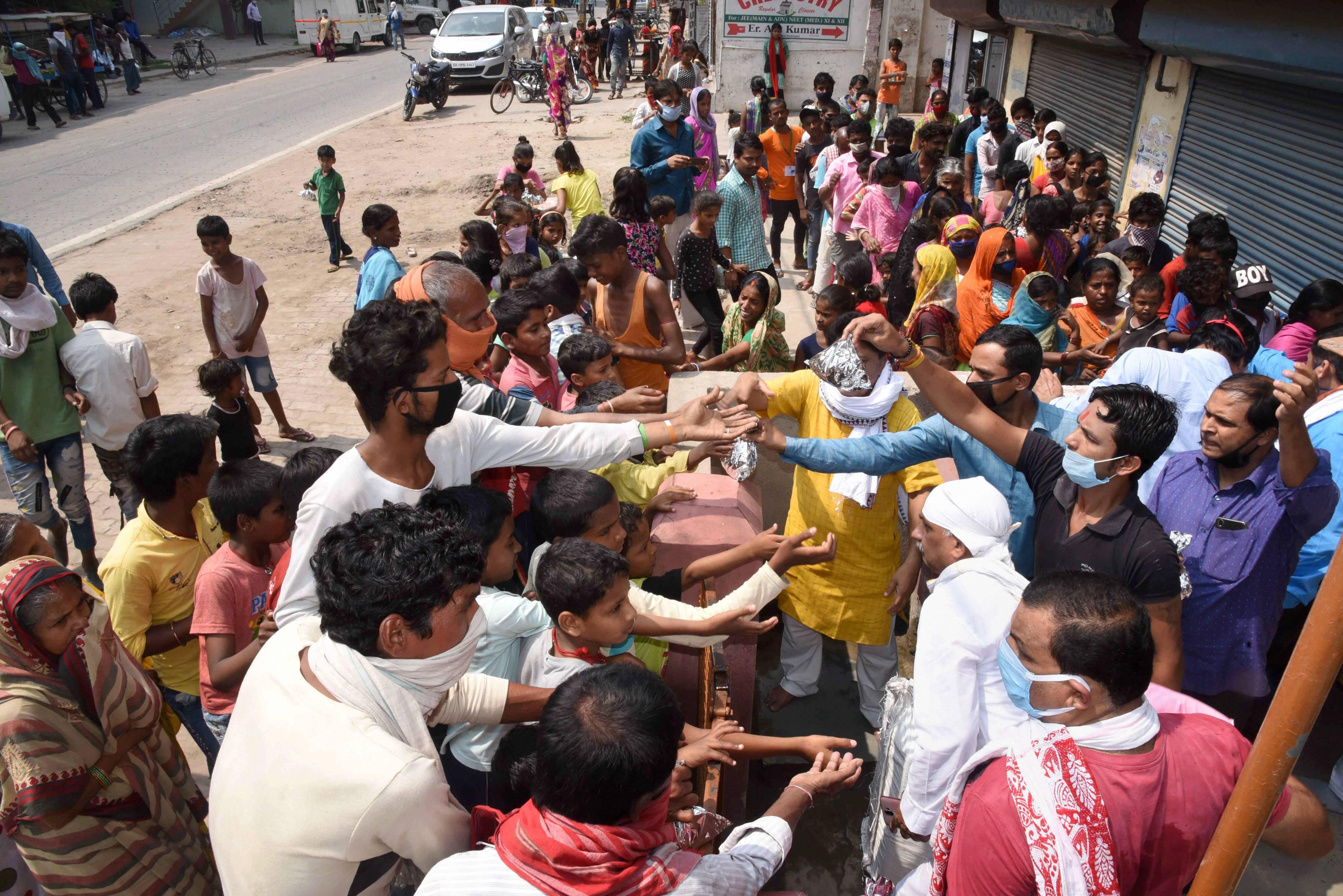 Volunteers distribute food to needy people during the nationwide lockdown, in wake of the coronavirus pandemic, in Patna.