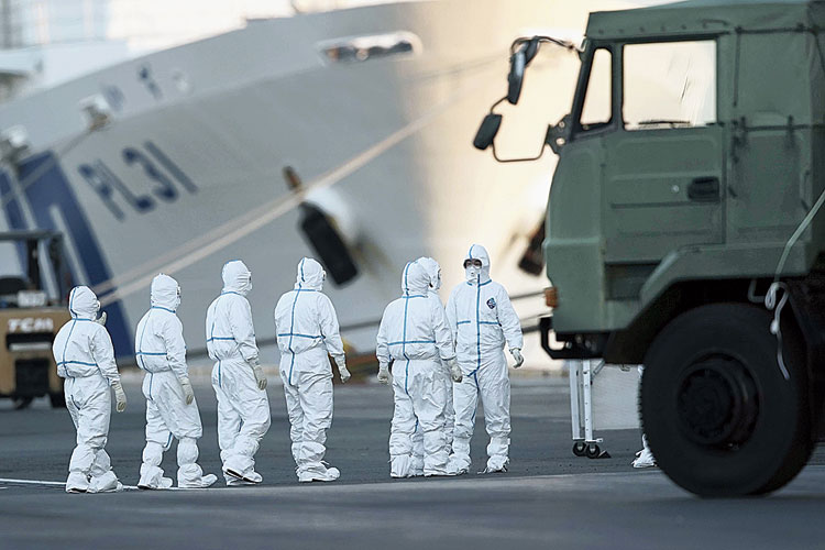 Officials in protective suits prepare to work around the quarantined Diamond Princess cruise ship in Yokohama on Monday.