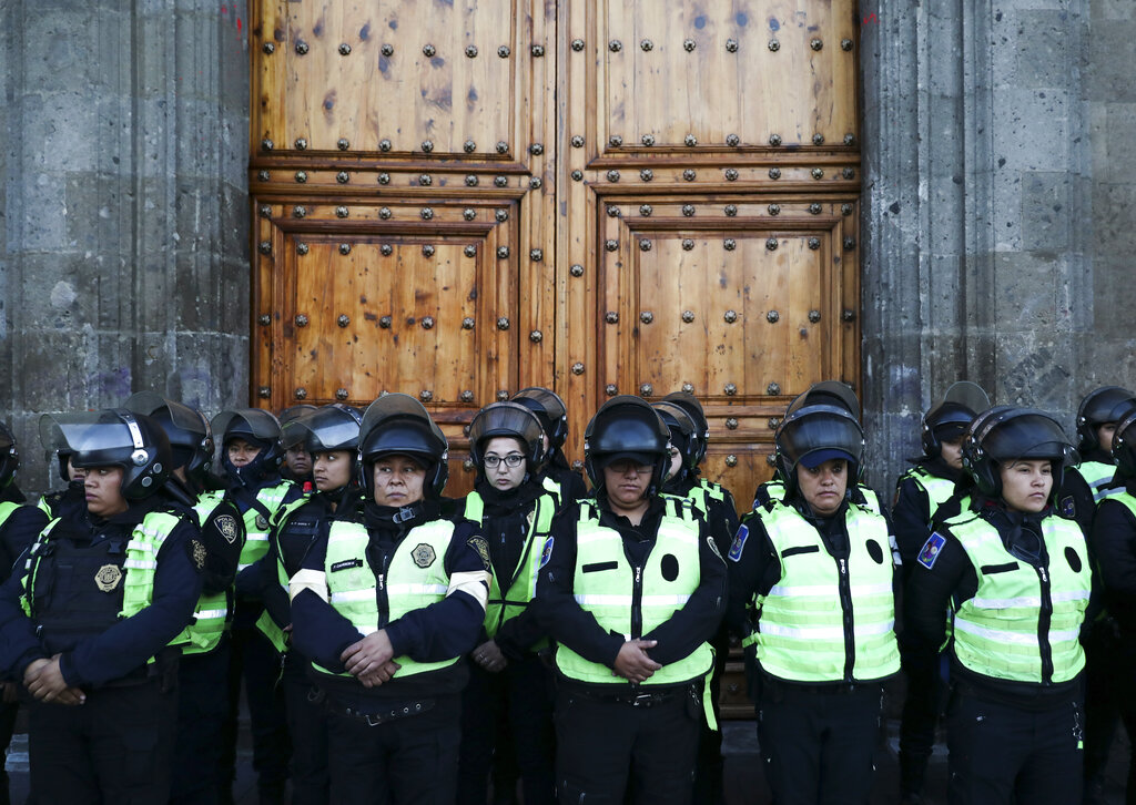 An 18 February, 2020 picture of police as they stand guard outside the National Palace, that includes the presidential residence and office, during a protest by women against gender violence in Mexico City, Tuesday. The killing of a 7-year-old girl on the southern outskirts of Mexico City has stoked rising anger over the brutal slayings of women, including one found stabbed to death and skinned earlier this month.