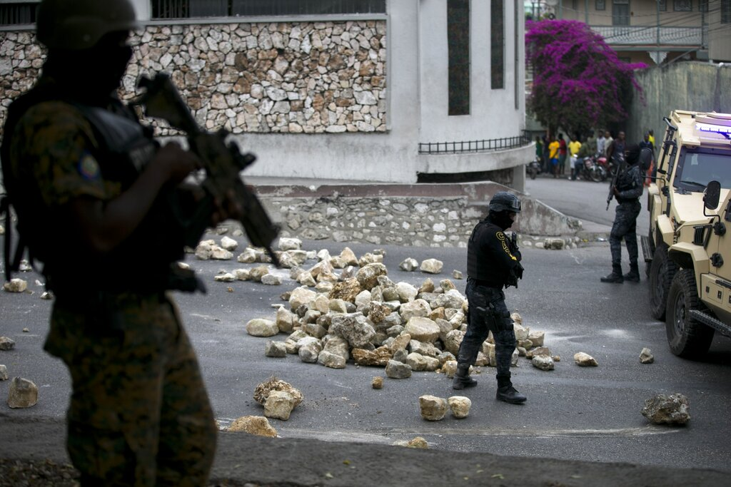 Police officers from the national palace remove a barricade on the road that leads to the house of President Jovenel Moise as off-duty police officers protest over pay and working conditions, in Petion-Ville, Haiti, on Monday. Police protests began this month after a half-dozen officers were fired over their attempt to unionize.