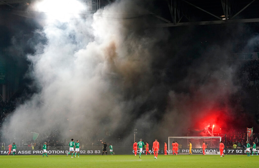 Saint-Etienne's fans light flares during the French League One soccer match between the club and Paris Saint-Germain in Saint-Etienne, France, on December 15
