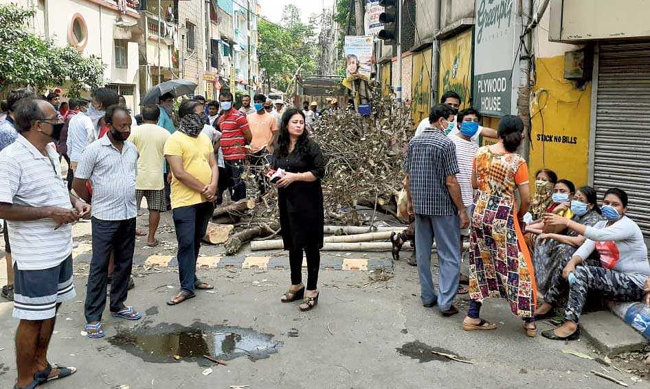 The group from Pallishree waits 20 yards away from the spot where the CESC workers were repairing cables at Suryanagar along NSC Bose Road on Sunday afternoon.