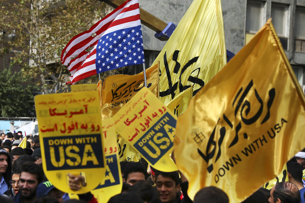 Demonstrators hold anti-US banners and a torn makeshift American flag upside down in an annual rally in front of the former the US Embassy in Tehran, Iran, Monday, November 4, 2019.