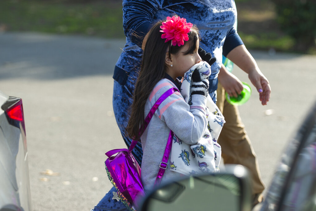 An unidentified girl covers her mouth as she evacuates the Park Avenue Elementary school in Cudahy, California, on January 14, 2020