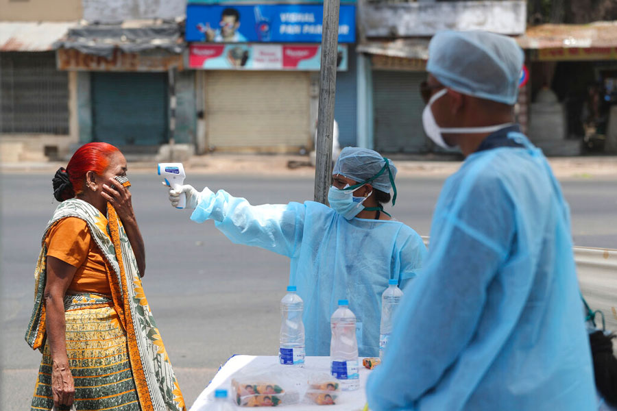 An Indian health worker checks the temperature of a woman during lockdown to prevent the spread of coronavirus in Ahmedabad on Wednesday
