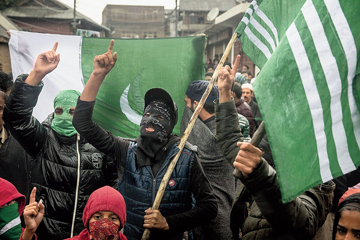 Masked Kashmiris shout slogans during a protest after Friday prayers on the outskirts of Srinagar on October 4, 2019.