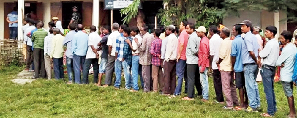 Voters queue up to cast their votes at a polling station in Sonari on Monday