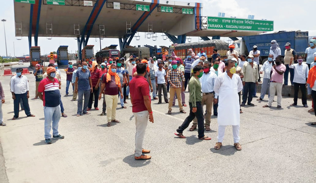 Workers protest over unpaid salaries in front of a toll plaza in Baishnabnagar near Malda last month.