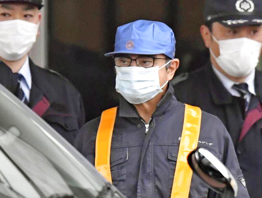 Carlos Ghosn, wearing a surgical mask and a blue cap, leaves the Tokyo Detention Centre on Wednesday.