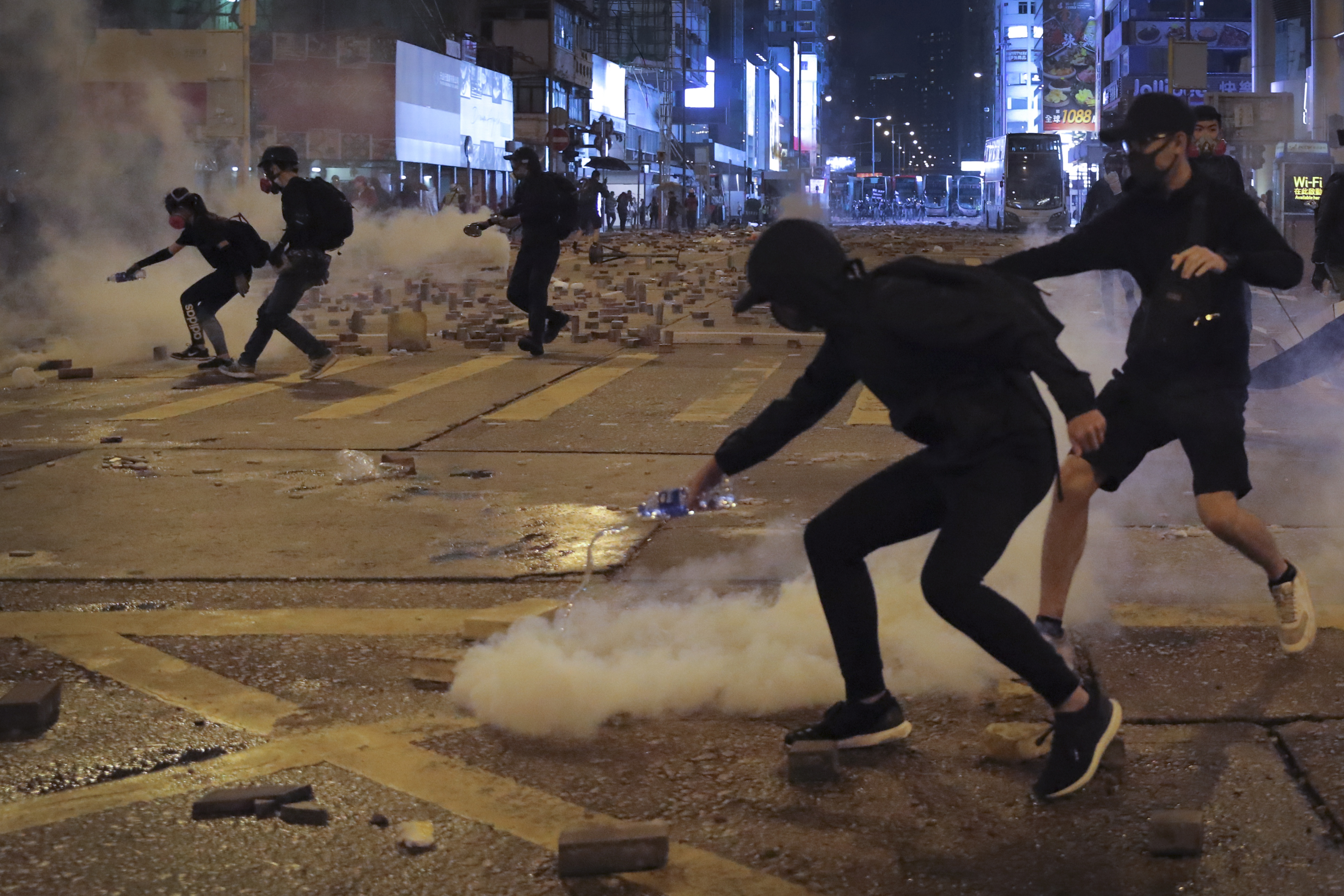 A protester pours water onto a tear gas canister fired by riot police on a street scattered with bricks, during a protest in Hong Kong, on November 11, 2019