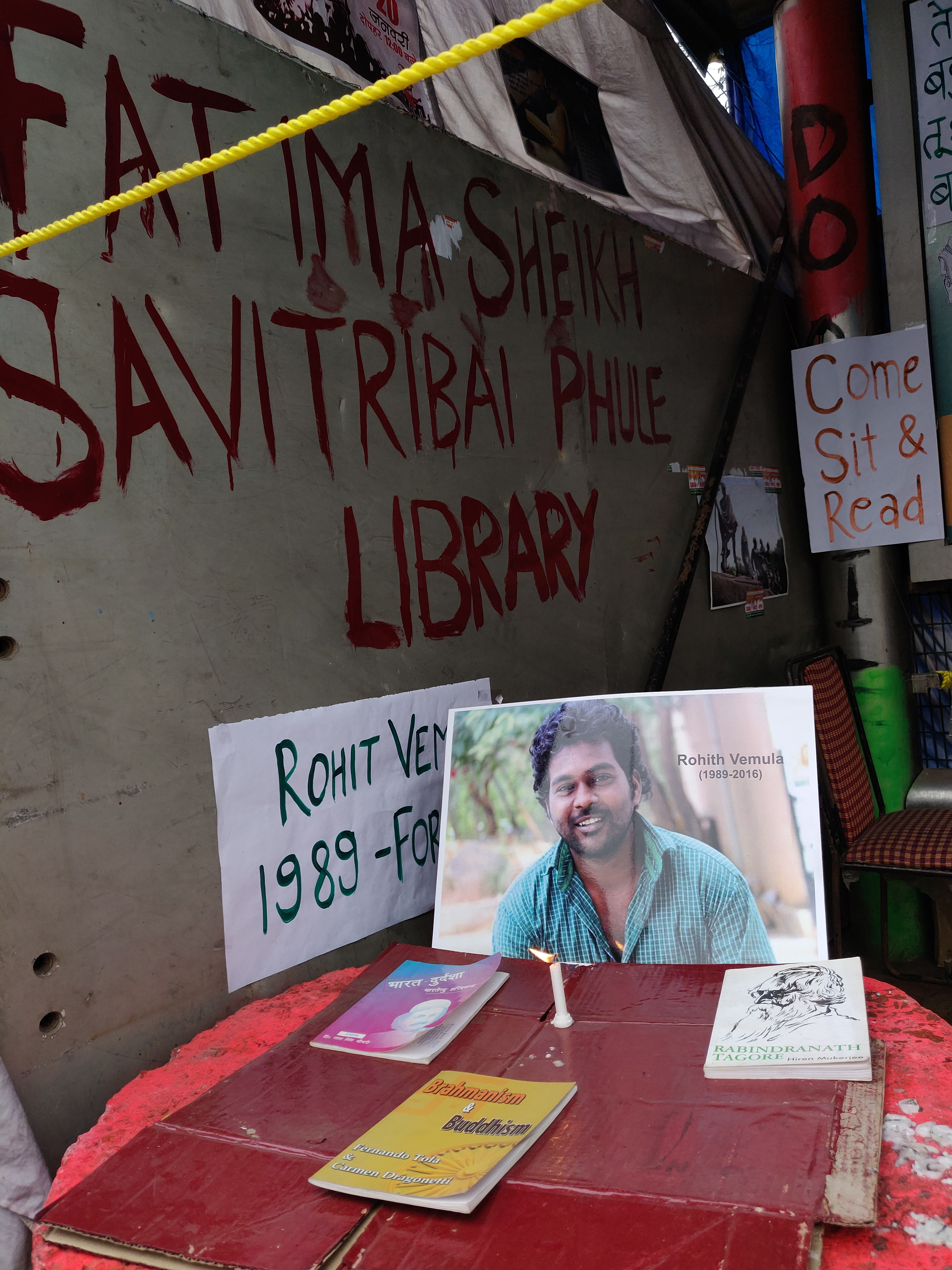 Rohith's portrait occupies one corner of the ragged library, a candle burns.