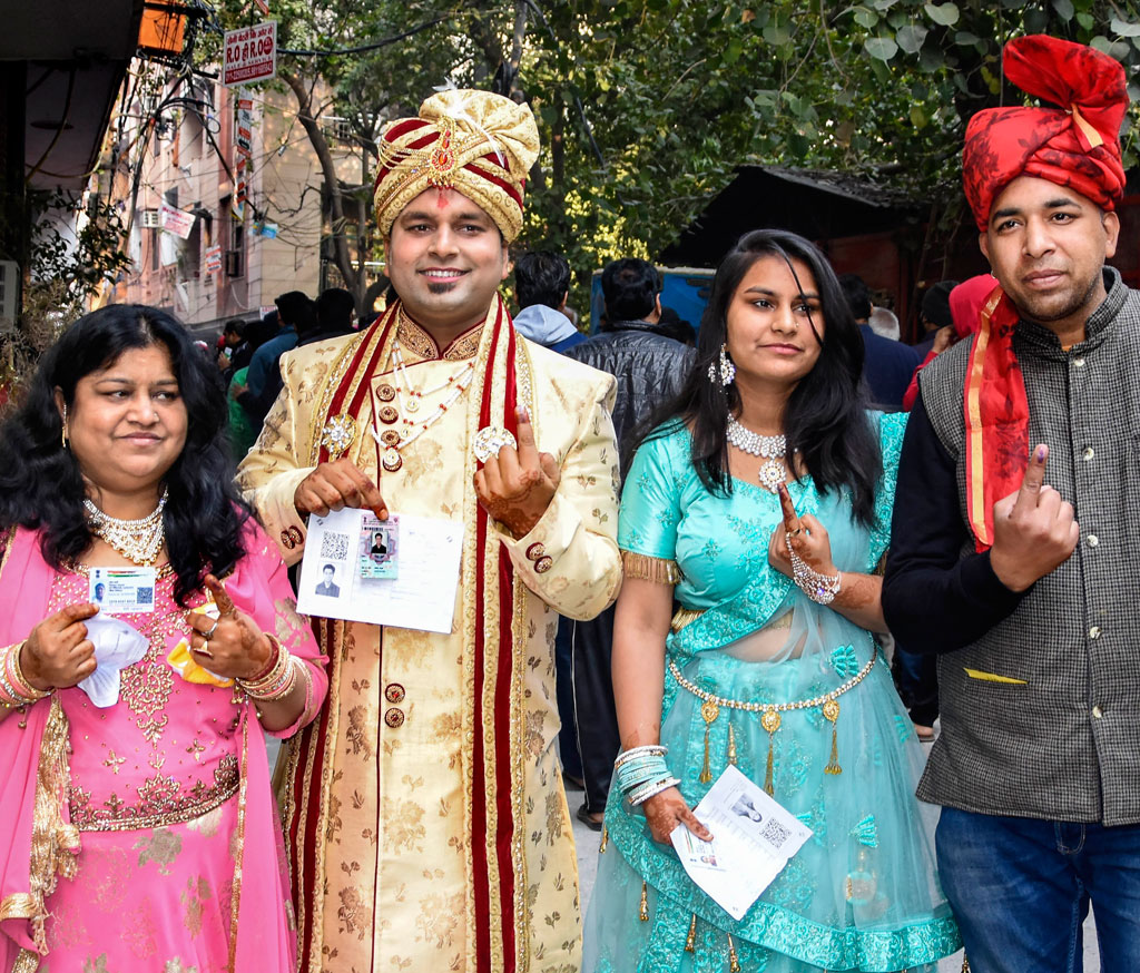 A groom and his family members after casting their votes for Delhi Assembly elections, at a polling station in east Delhi, on Saturday