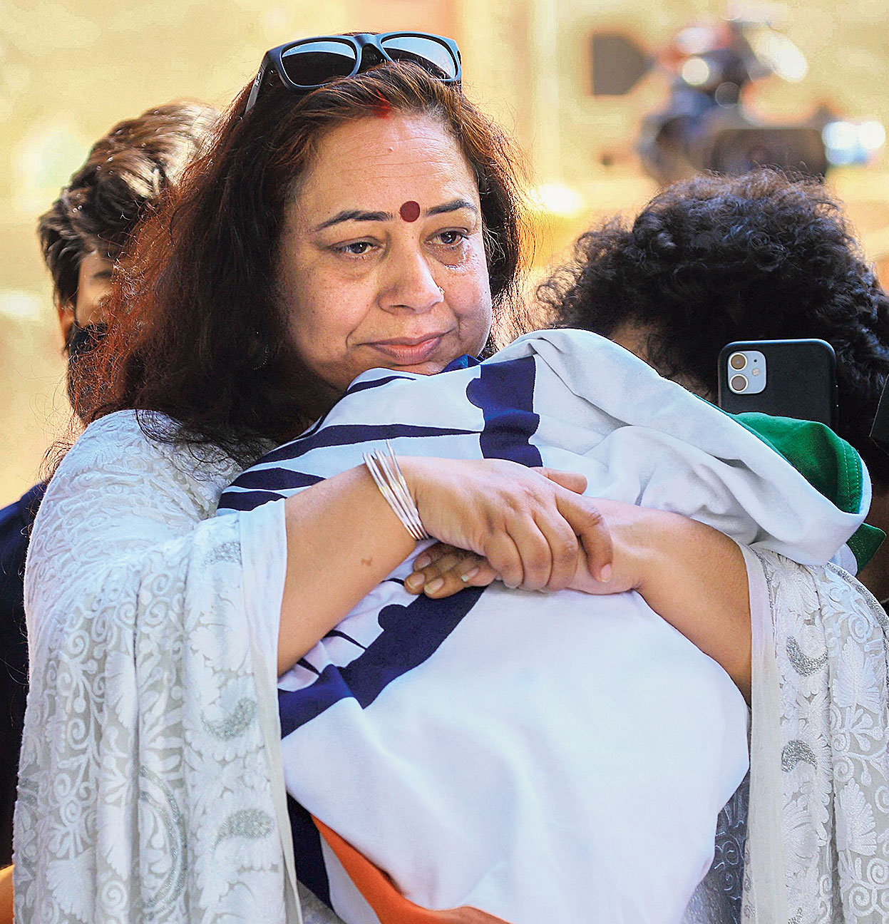 Pallavi Sharma, wife of Colonel Ashutosh Sharma, hugs the Tricolour that had draped her husband's body at his funeral in Jaipur on Tuesday. The commanding officer of 21 Rashtriya Rifles was killed in a gunfight with militants in Kashmir on Sunday.