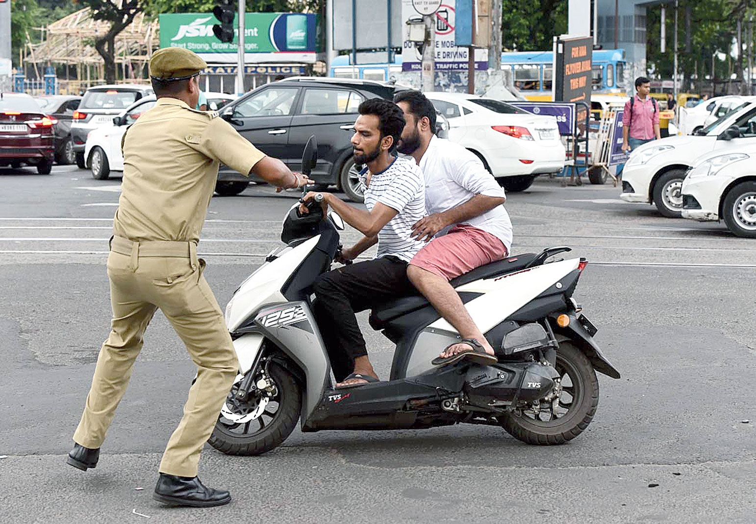 A homeguard tries to stop a man riding a two-wheeler without helmet during a crackdown on unruly bikers at Park Circus seven-point crossing on  Thursday afternoon.