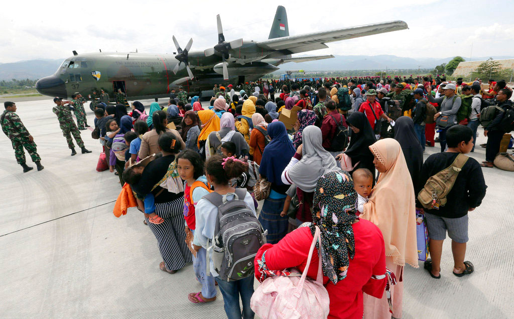 People line up to board an Air Force cargo plane at the Mutiara Sis Al-Jufri airport to evacuate the earthquake and tsunami-damaged city of Palu, Central Sulawesi Indonesia, on Thursday.