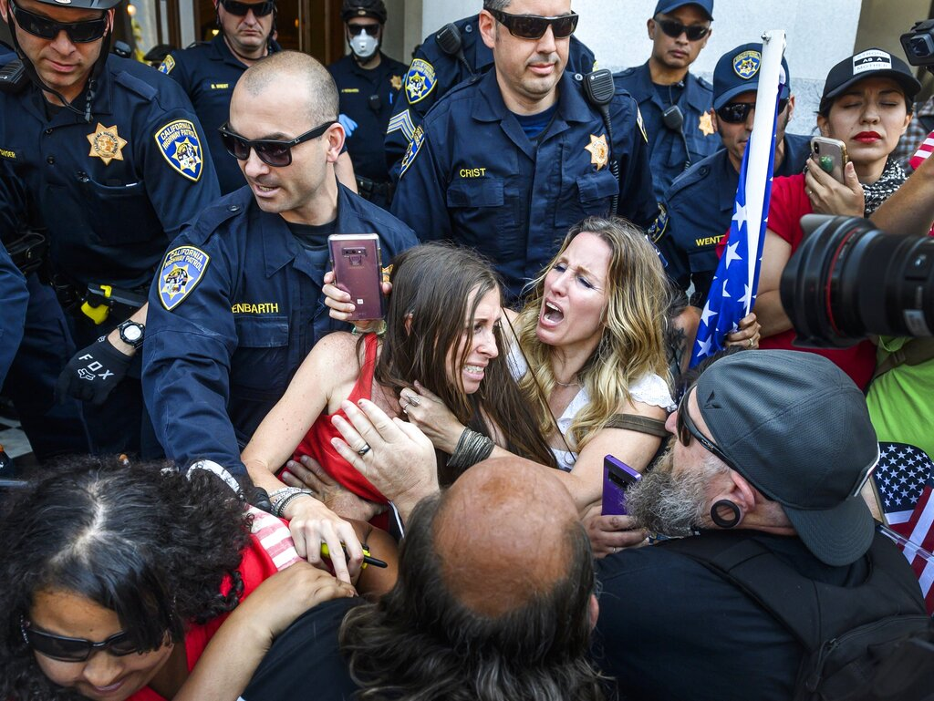 In this Friday, May 1, 2020 photo, protester Heidi Munoz Gleisner, center left, is removed from a demonstration against California Gov. Gavin Newsom's stay-at-home order by California Highway Patrol officers after they ordered a crowd of people to leave the Capitol grounds in Sacramento, California.