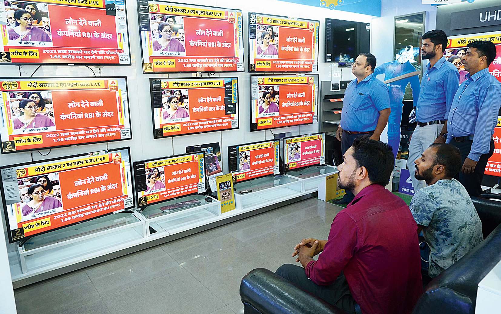People watch the budget at an electronics showroom in Ranchi on Friday.