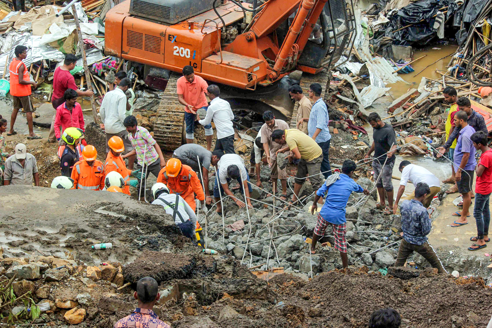 NDRF and fire brigade personnel look through debris after a portion of a compound wall collapsed on shanties adjacent to it at Malad East in Mumbai on Wednesday