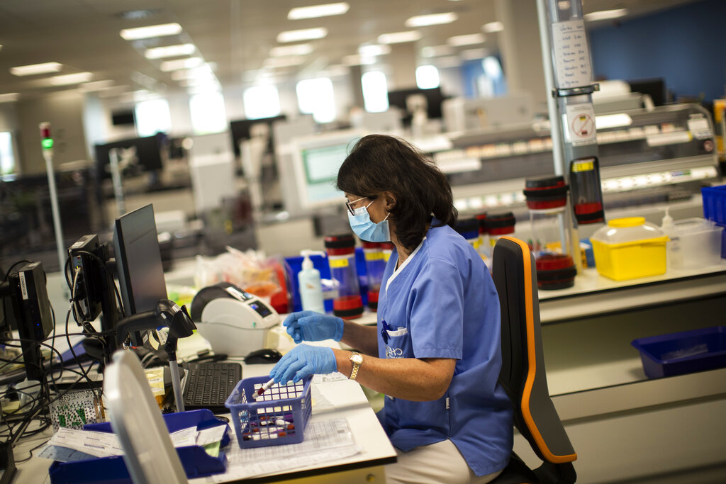 A member of medical personnel works with samples in a lab at the MontLegia CHC hospital, during a gradual lifting of a lockdown to prevent the spread of the coronavirus, in Liege, Belgium, Friday, May 8, 2020.