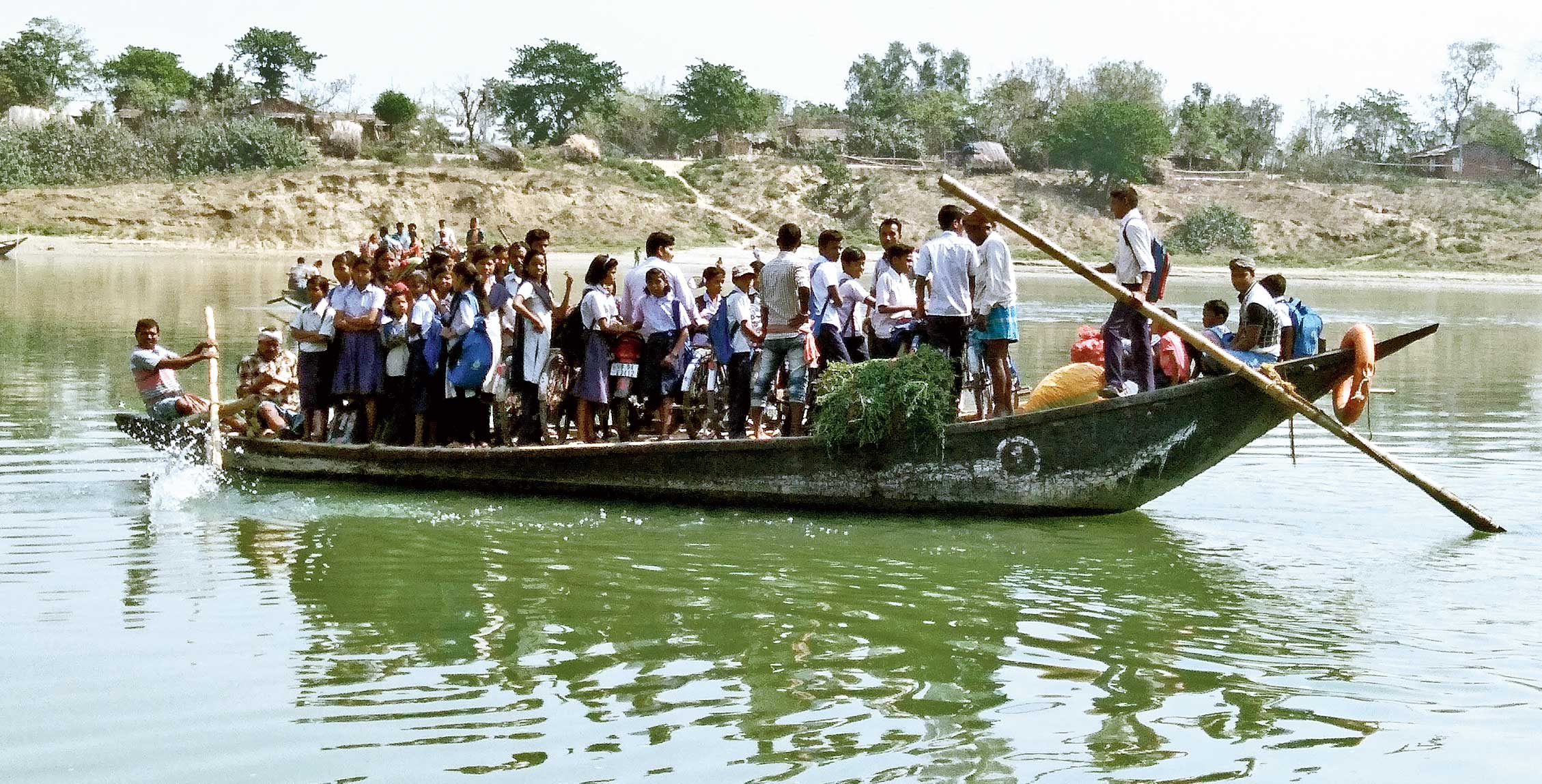 School students cross the canal on a boat in Suti.