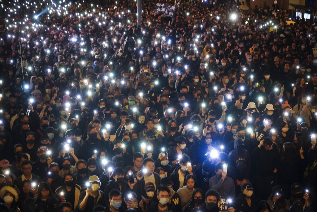 Pro-democracy protesters flash their smartphones lights as they gather on a street in Hong Kong, Sunday, Dec. 8, 2019.