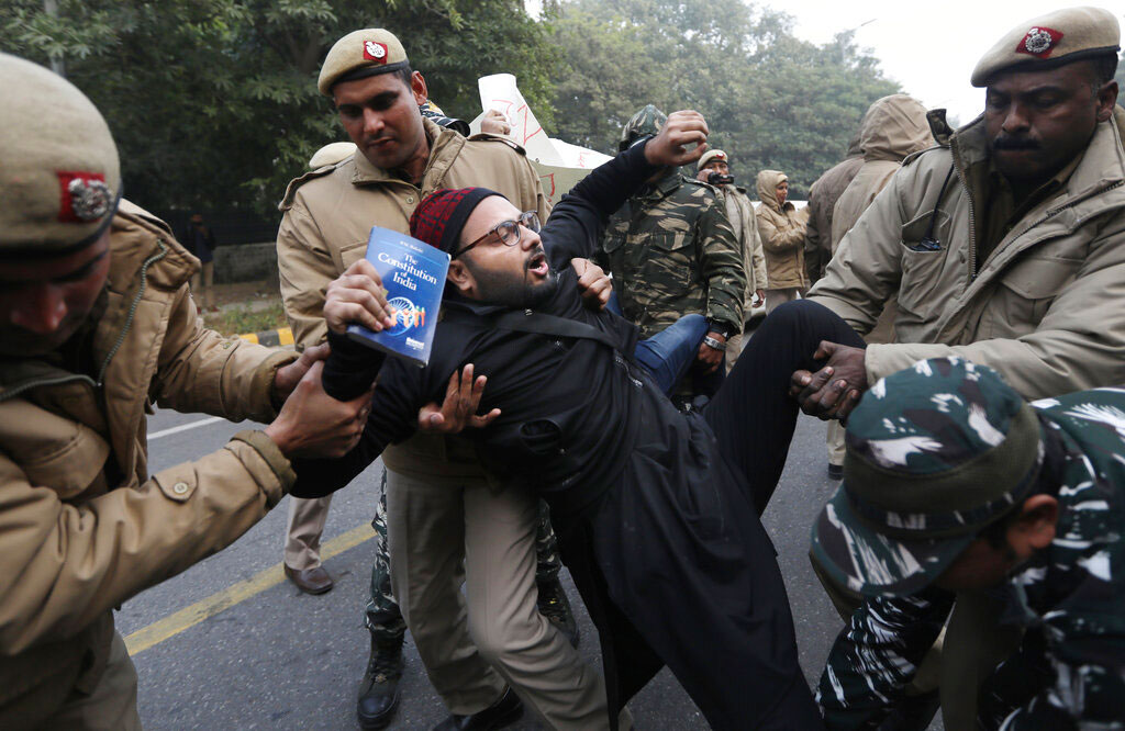 Police officers detain a protesting student outside Uttar Pradesh Bhawan during a protest against the amended citizenship act in New Delhi on Friday.