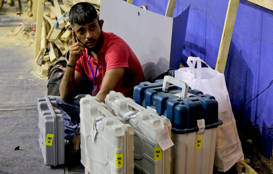 A polling officer sits with Electronic Voting Machines at a distribution centre in Kolkata on Saturday, May 18, 2019.