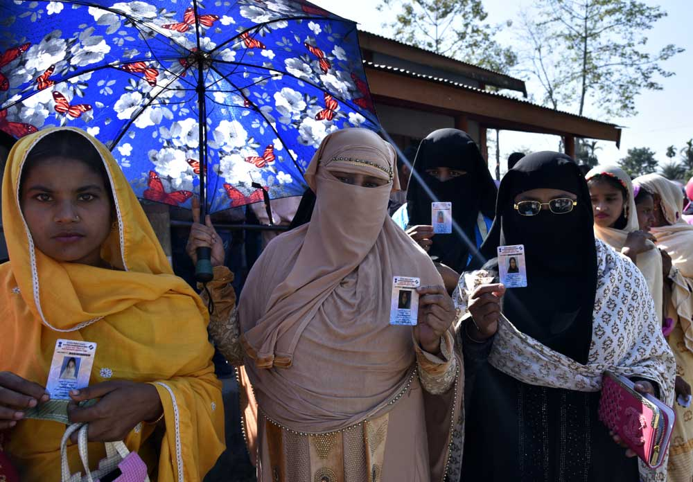 Women voters show their voter ID cards while standing in a queue at a polling station during the 2nd phase of the panchayat elections in Barpeta, Assam on December 9, 2018.