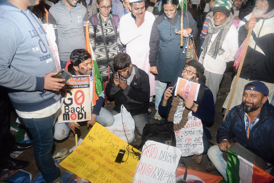 "A group of protesters staging a skit on JL Nehru Road on Saturday evening. ""I am the first Prime Minister to have lied from the Red Fort….,"" said one of them, his face hidden by a Modi mask"