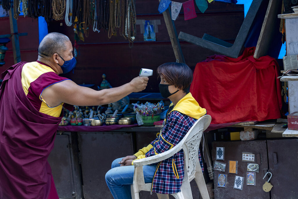 An exiled Tibetan Buddhist monk uses a digital probe thermometer to measure the body temperature of a roadside vendor in Dharmsala, India, Sunday, May 24, 2020. He has been walking around the town for the past one week checking people's temperature as part of community service.