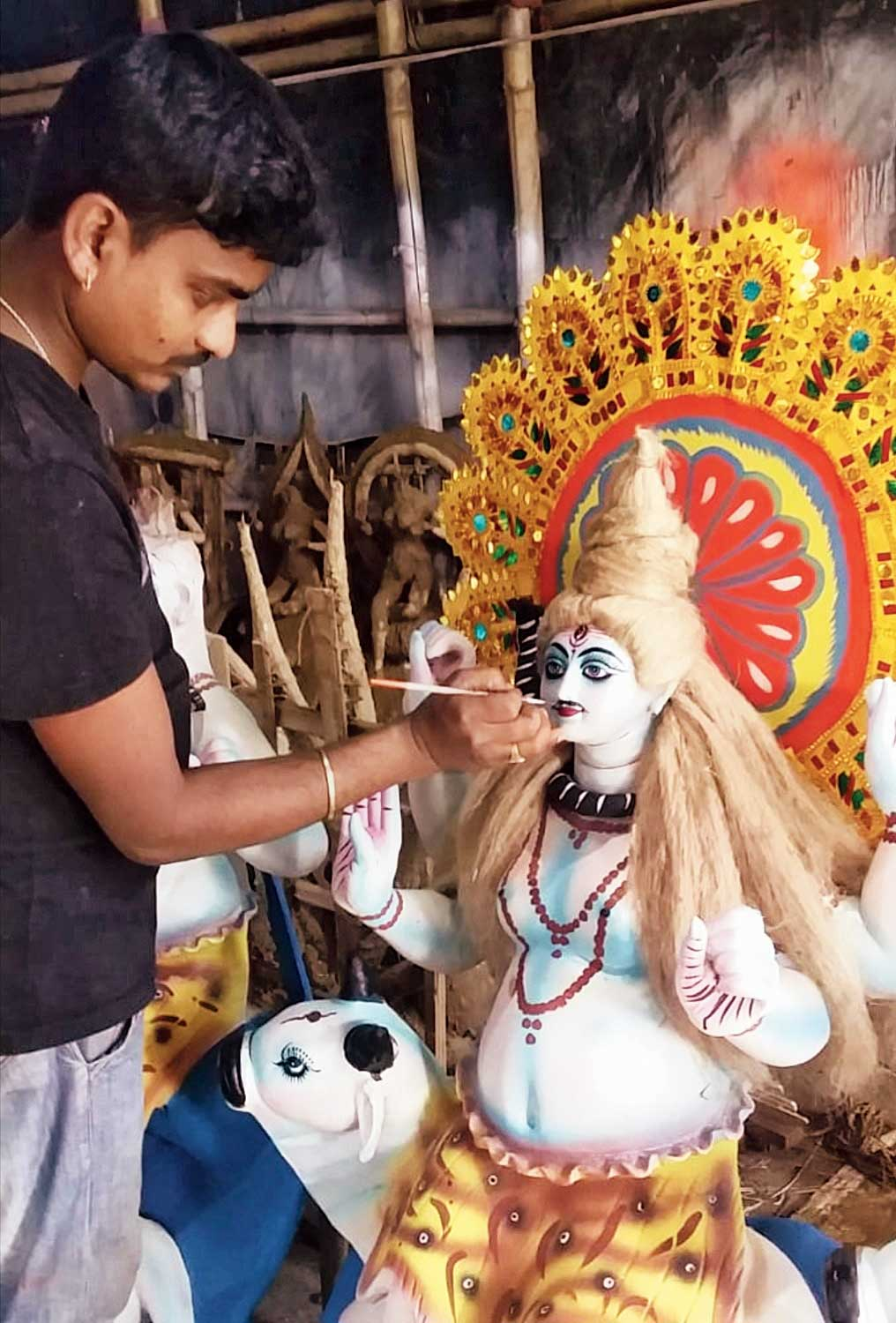 An artisan gives finishing touches to a Shiva idol in Doomdooma.
