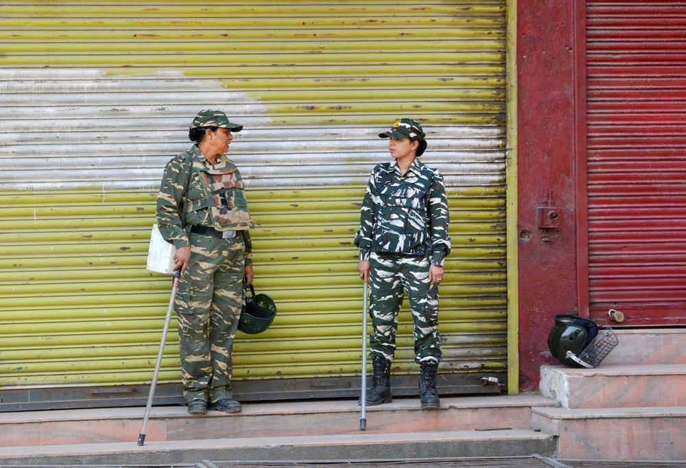 Security personnel stand guard at a closed market during restrictions to maintain law and order, in Srinagar, Sunday, September 01, 2019.