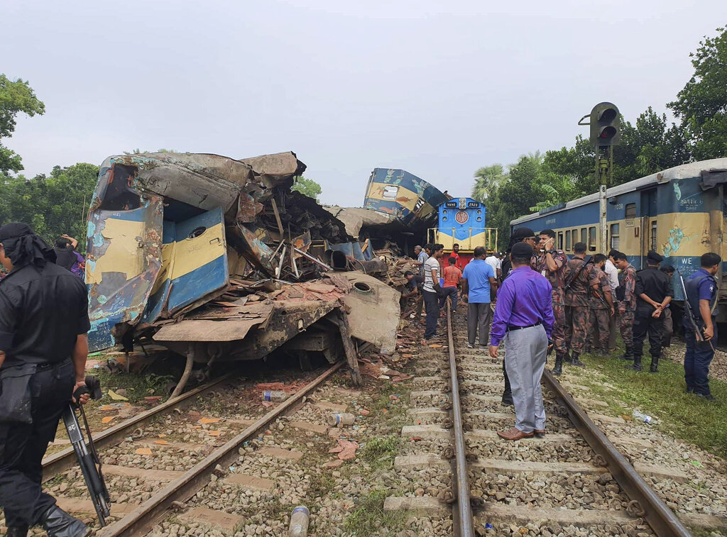 People gather near damaged coaches of two trains after they collided in Brahmanbaria district, 82 kilometers east of the capital Dhaka, Bangladesh, Tuesday, November 12, 2019.