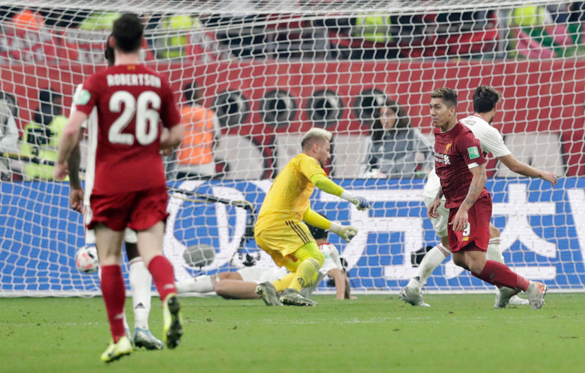 Liverpool's Roberto Firmino, right, scores his sides first goal past Flamengo's goalkeeper Diego Alves, center, during the Club World Cup final soccer match between Liverpool and Flamengo at Khalifa International Stadium in Doha, Qatar, Saturday