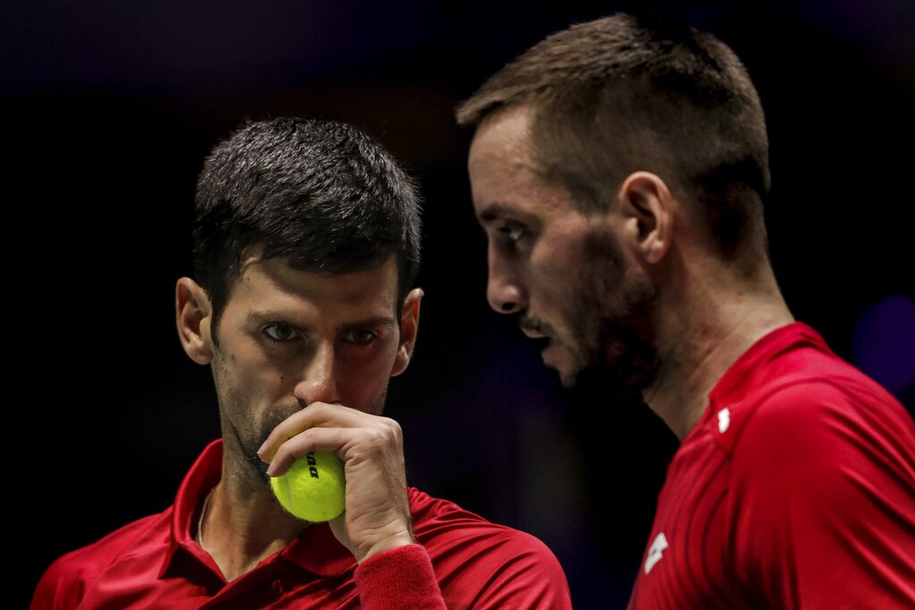 In this Nov. 22, 2019, file photo, Serbia's Novak Djokovic, left, and teammate Viktor Troicki play against Russia's Karen Khachanov and Andrey Rublev during the Davis Cup quarterfinal doubles match in Madrid, Spain.