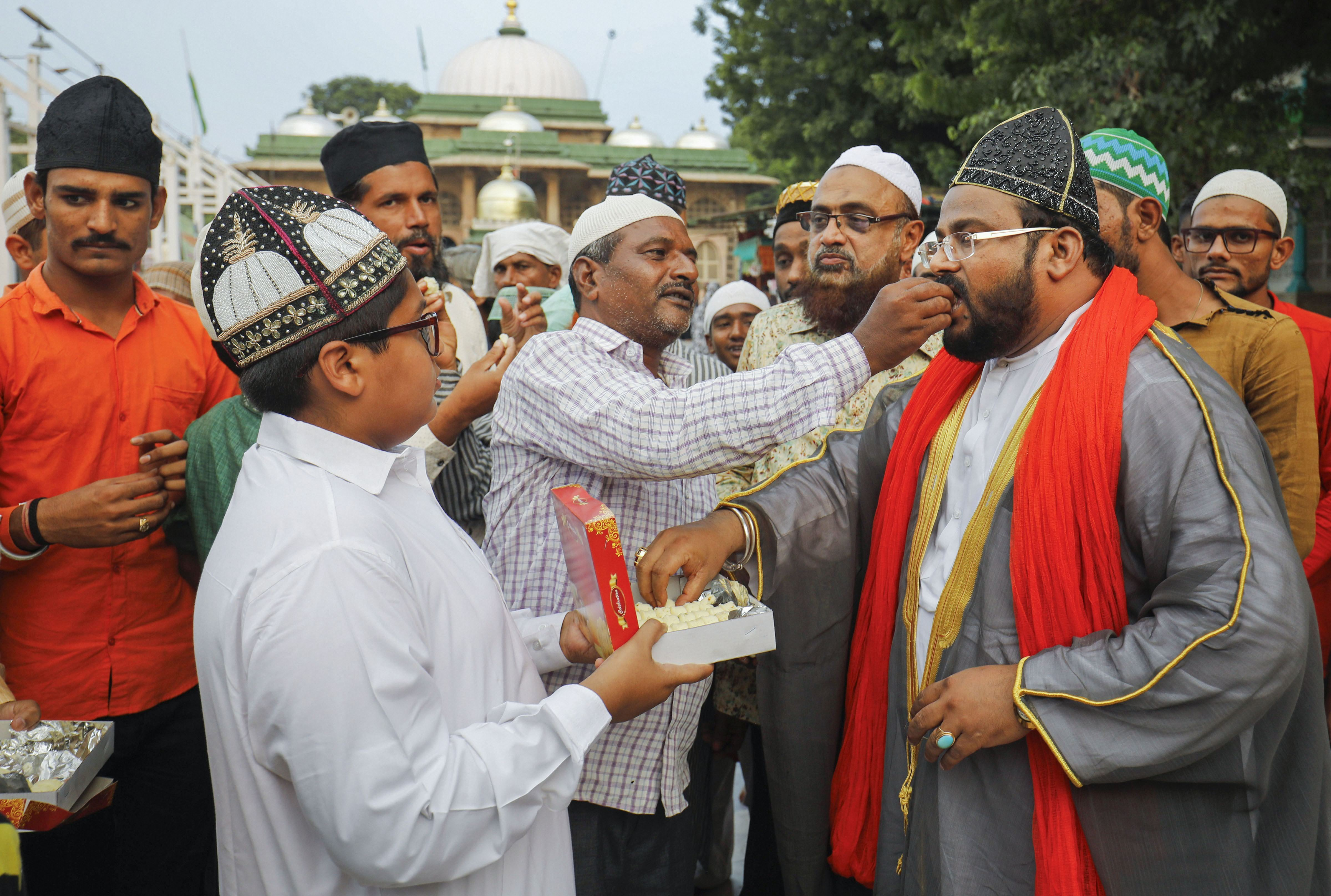 Muslims offer sweets to each other after the Supreme Court's verdict on the Ayodhya case, outside the Shah-e-alam shrine in Ahmedabad, Saturday, November 9, 2019.
