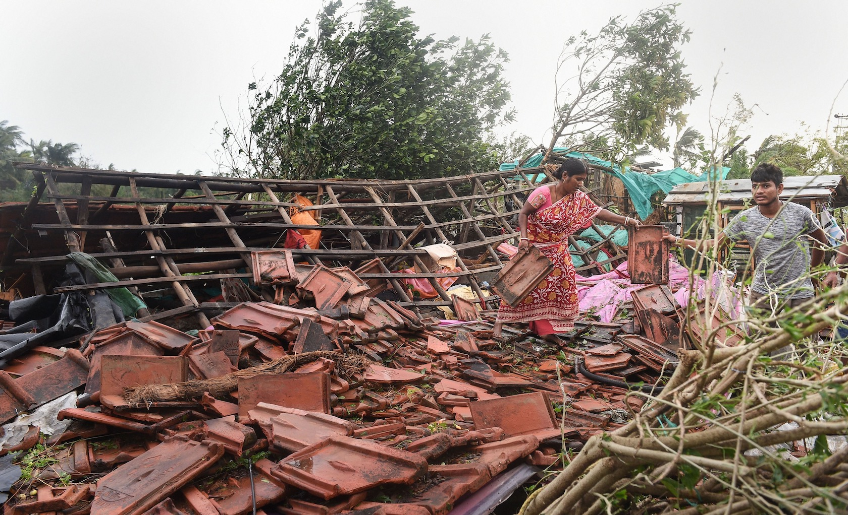 A woman stands on the remnants of her house in the aftermath of Cyclone Bulbul, at Bakkhali in the South 24 Parganas district of West Bengal, on Sunday, November 10, 2019