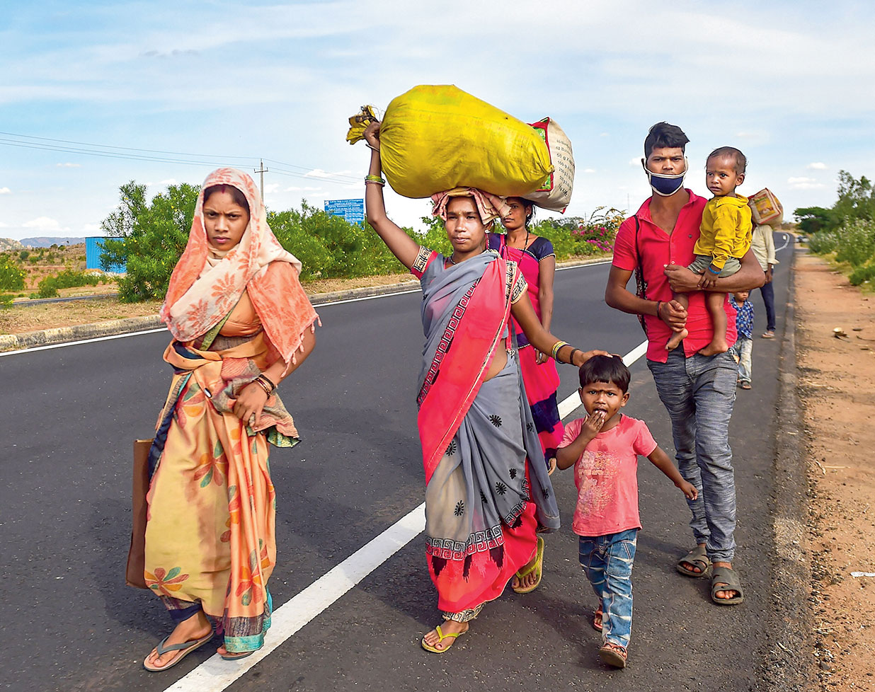 A migrant family from Chhattisgarh walks on the national highway at Devanahalli near Bangalore on May 15 as they make their way back home during the lockdown.