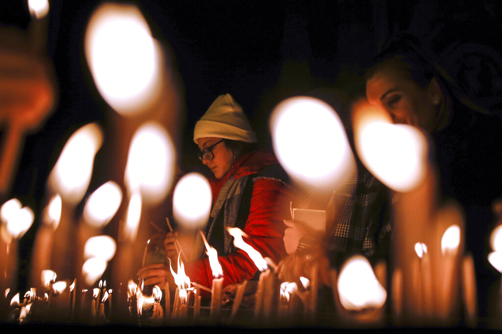 Catholic Christians light candles as they participate at a Christmas Eve Mass in St. Antoine Church, the largest church of the Roman Catholic Church, in Istanbul, Tuesday, Dec. 24, 2019.