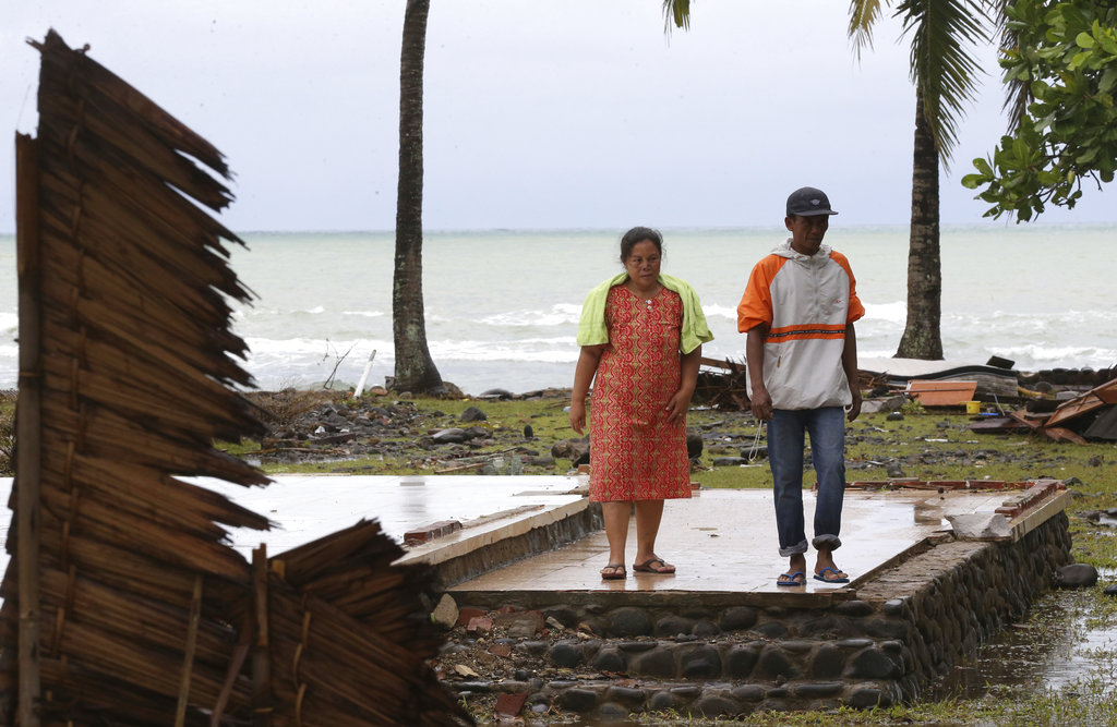 A tsunami survivor walks through the ruins of a villa with her husband in Carita, Indonesia, on Wednesday.