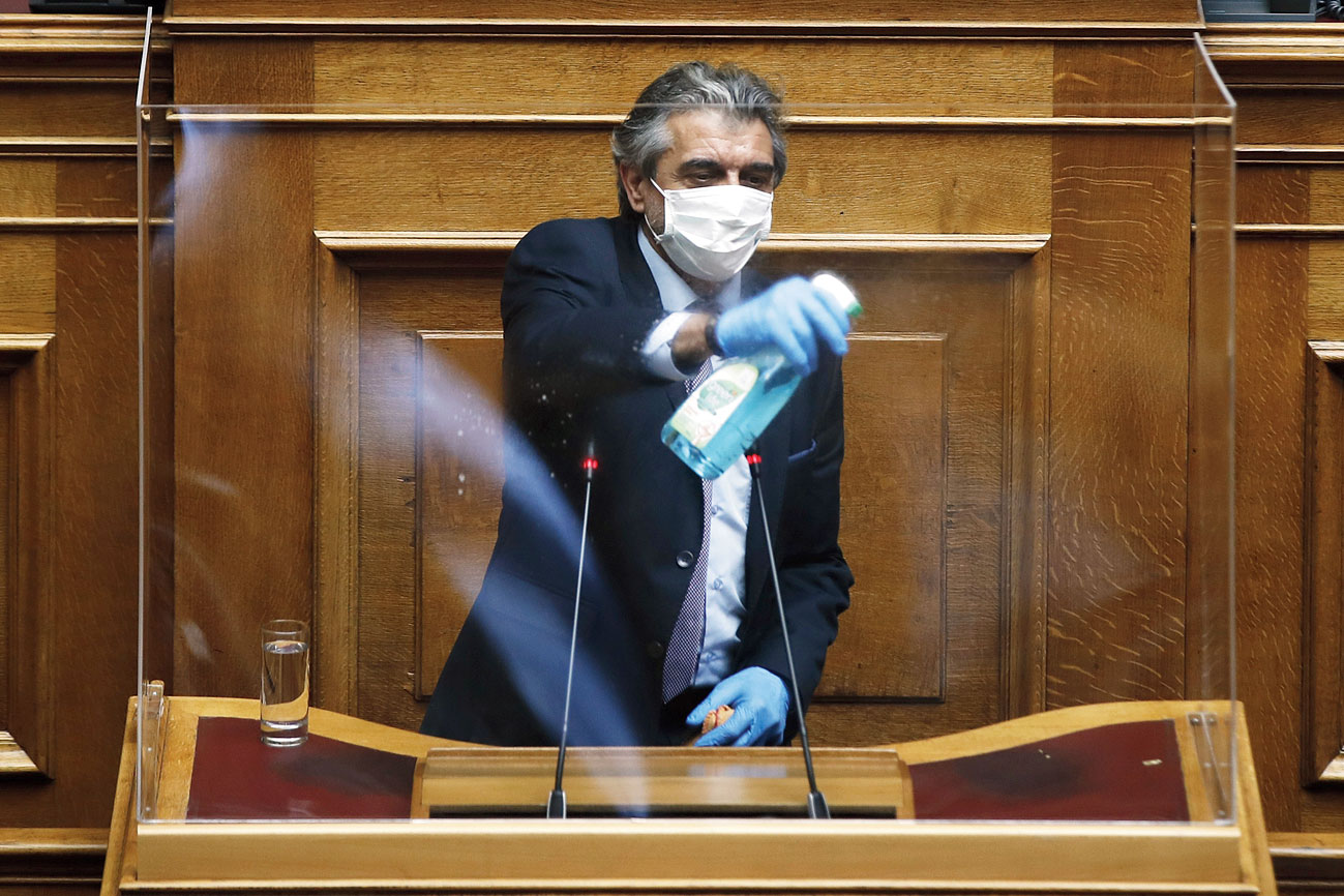 A Greek parliament employee disinfects a protective plastic shield in Athens.