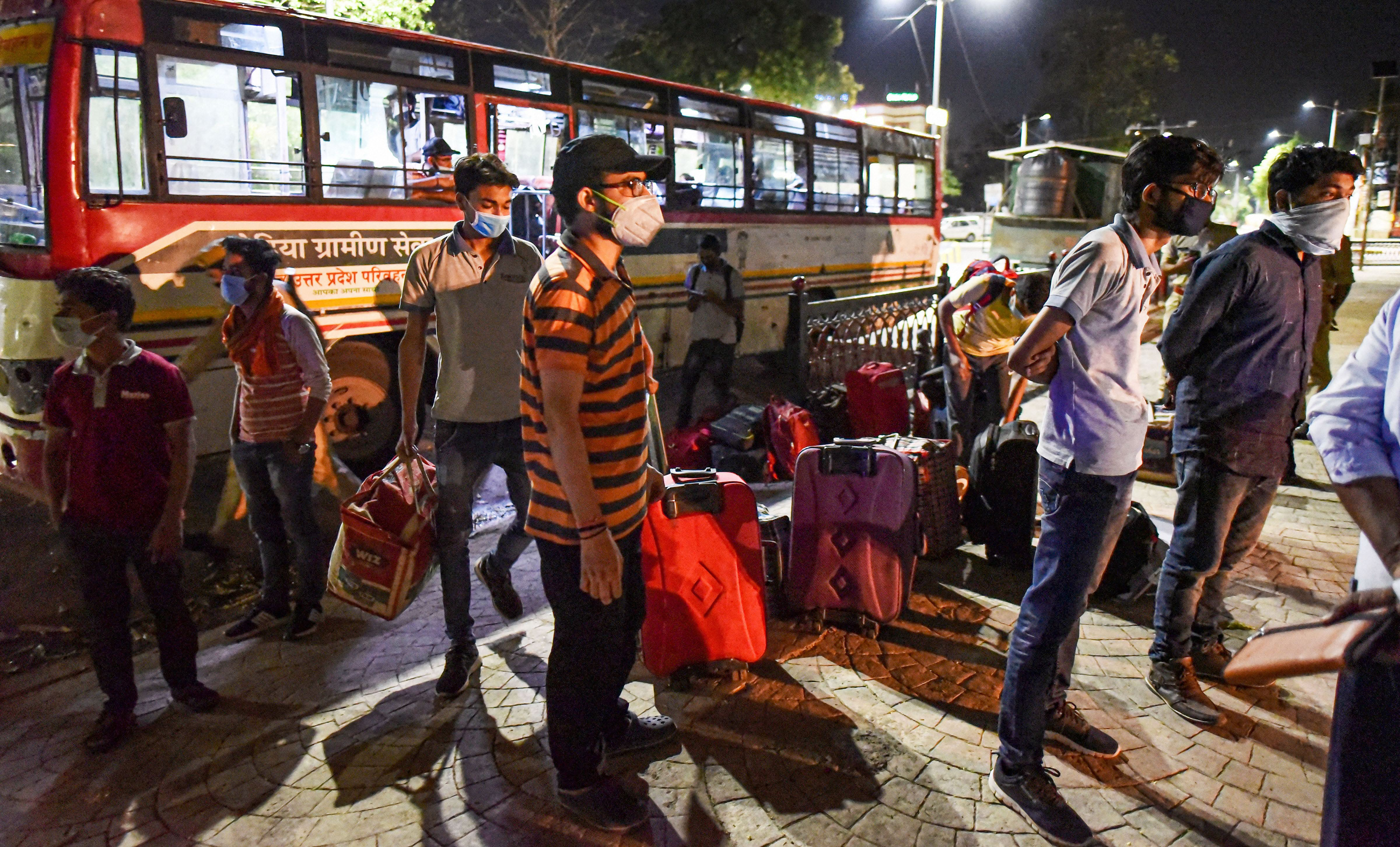 Stranded students from Kota alight the bus arranged by UP government as they arrive at their native place during the nationwide lockdown, imposed as a preventive measure against the coronavirus, in Prayagraj, Monday, April 20, 2020.