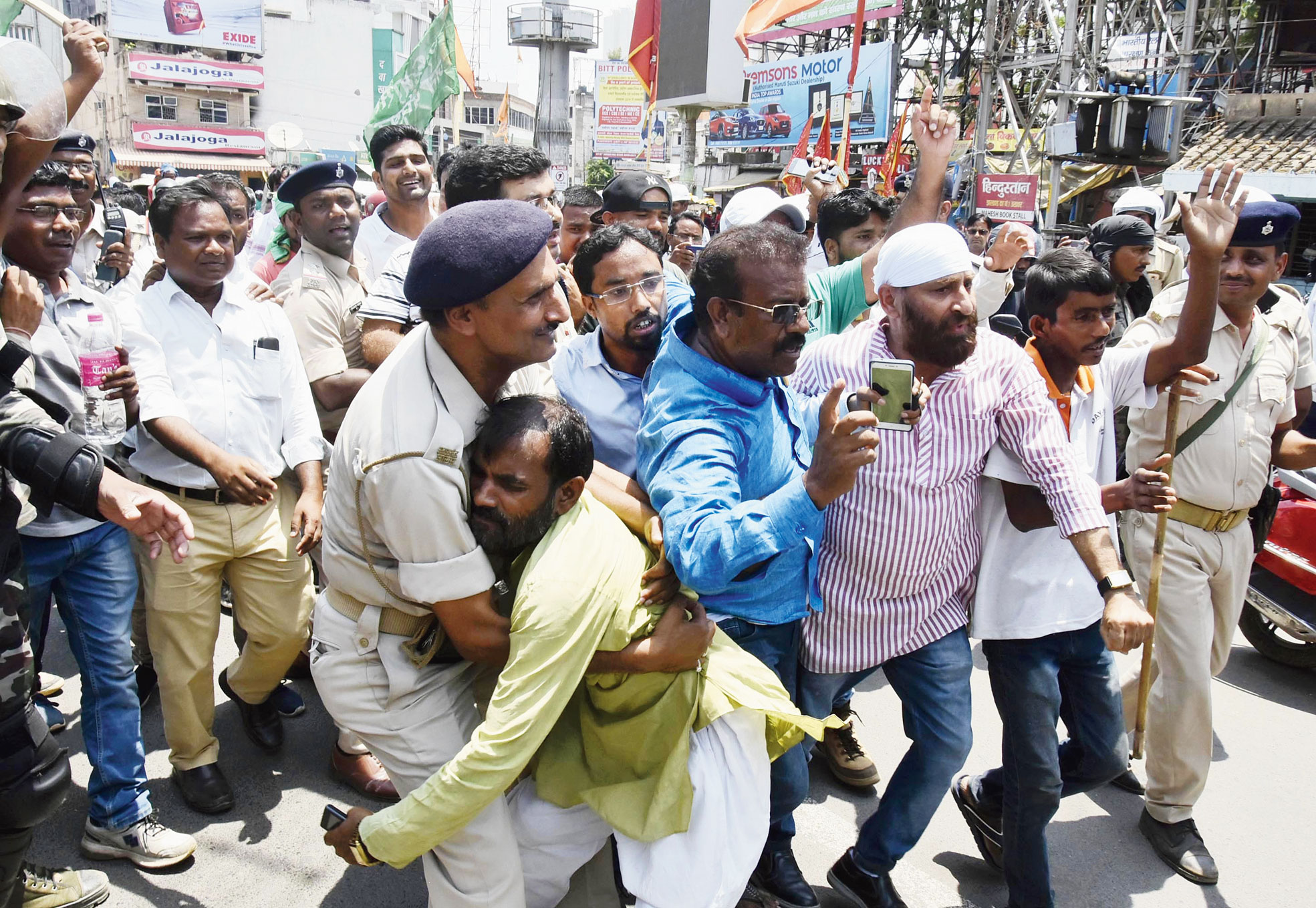 A policeman arrests a bandh supporter on Main Road in Ranchi on Saturday.