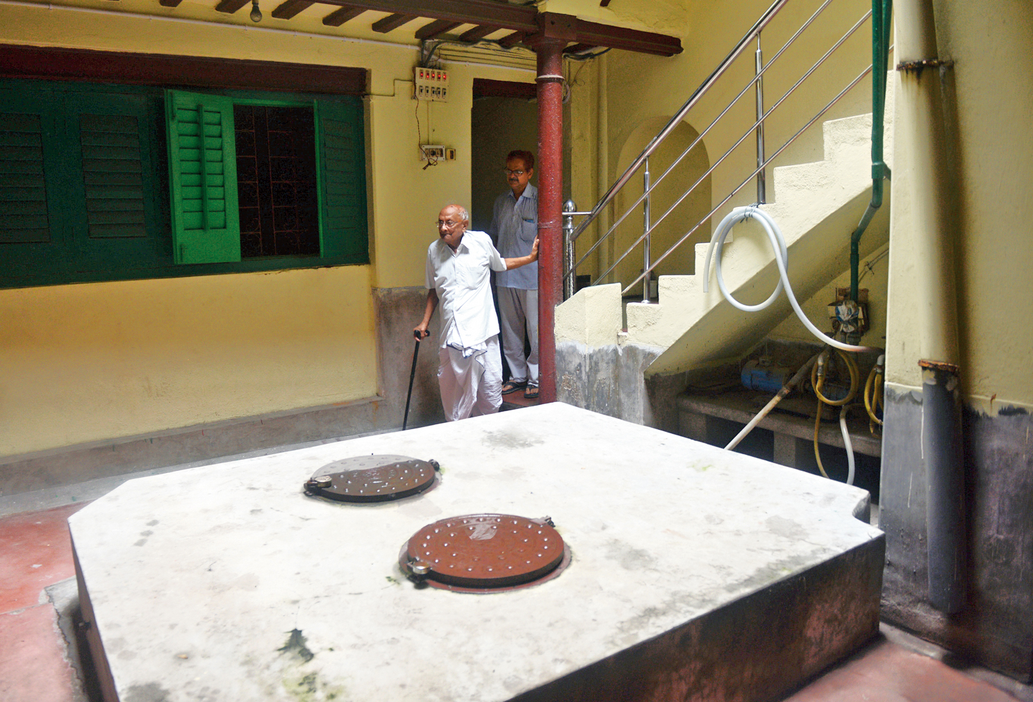 From the Mookerjee godown, two hackney carriages delivered the arms to the house of Bhujanga Dhur in Jelia Para Lane. The tank was not there in 1914 and the arms were kept in the courtyard, said Barendra Chandra Dhur (the elderly man with a walking stick), Bhujanga Dhur's nephew.  From the Dhur house, the arms were distributed to various groups of revolutionaries