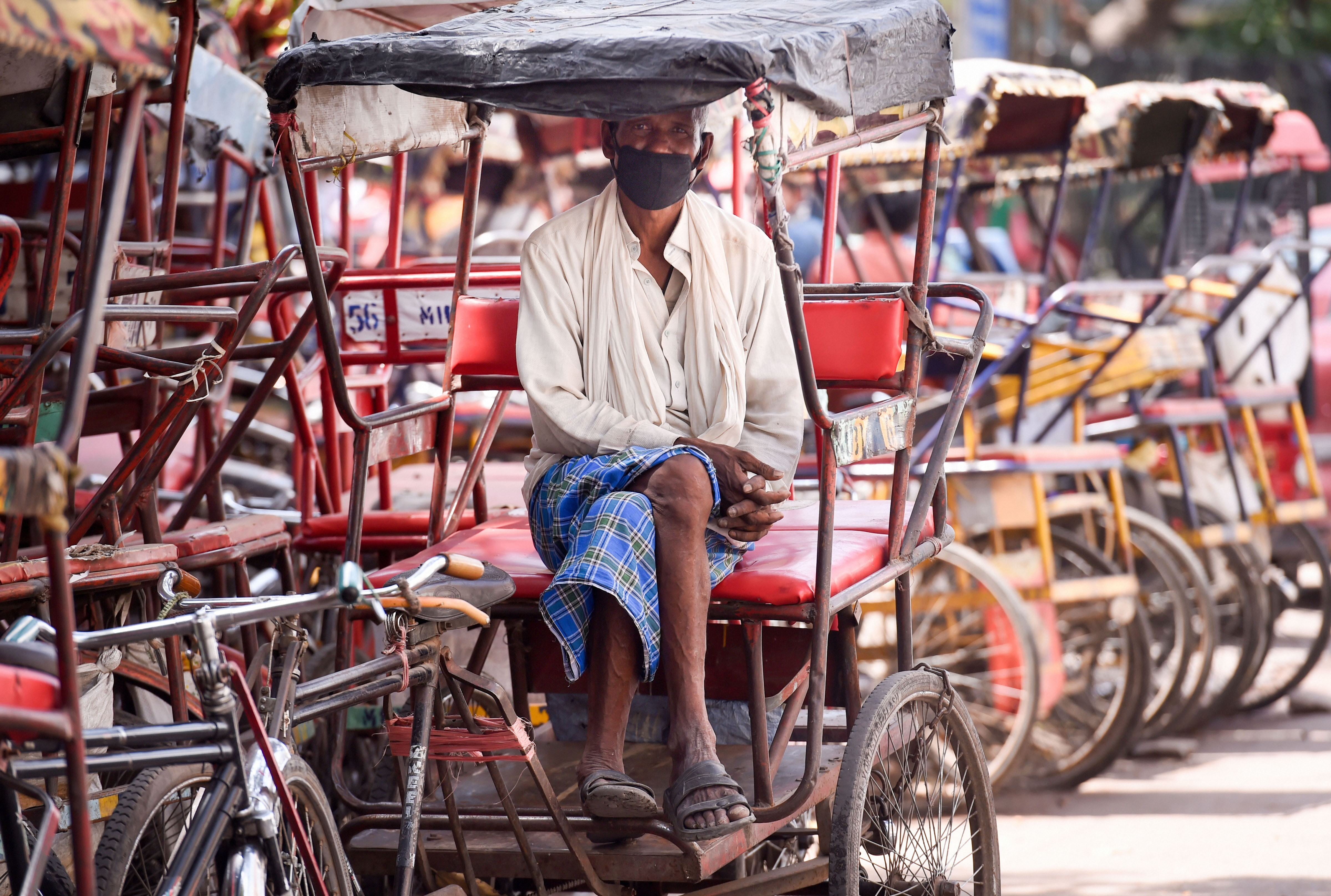 A rickshaw puller poses for the photographer during the nationwide lockdown to curb the spread of coronavirus, in Old Delhi, Friday, April 10, 2020. Delhis rickshaw pullers-- mostly migrants from Bihar and UP face a dire challenge with no work due to the ongoing lockdown.